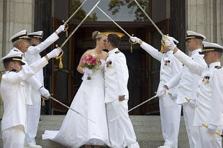 Military wedding with couple under arch of swords